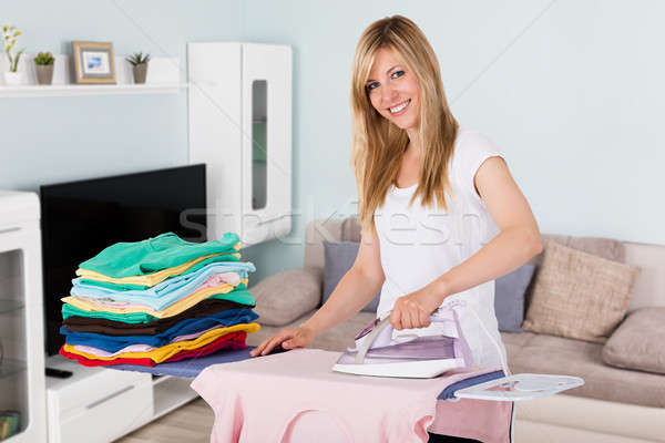 Happy Woman Ironing Clothes With Electric Iron Stock photo © AndreyPopov