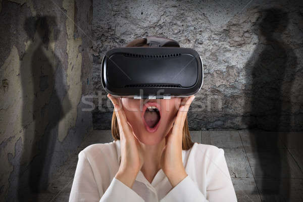 Afraid Woman Wearing Virtual Reality Glasses With Mouth Open Stock photo © AndreyPopov