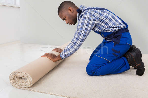 Male Handyman Rolling Carpet Stock photo © AndreyPopov