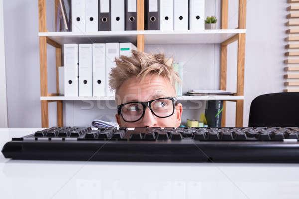 Grappig zakenman verbergen achter bureau Stockfoto © AndreyPopov