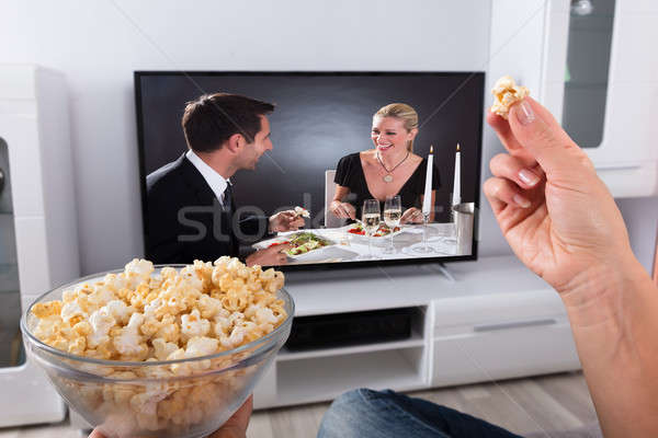 Person's Hand Holding Popcorn While Movie Plays On Television Stock photo © AndreyPopov