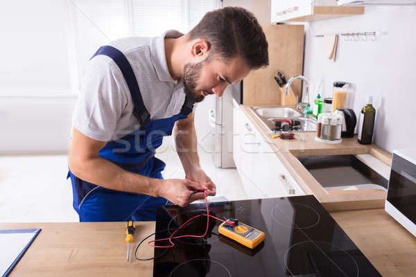 Young Repairman Fixing Induction Stove Stock photo © AndreyPopov