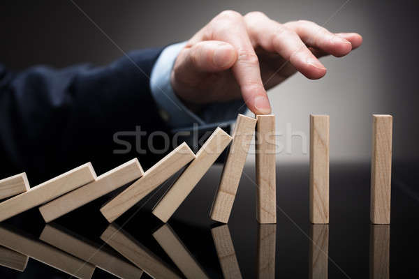 Businessperson Stopping Wooden Blocks From Falling On Desk Stock photo © AndreyPopov