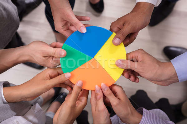 Businesspeople Holding Pie Chart Stock photo © AndreyPopov