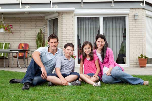 Happy family relaxing in backyard of new home Stock photo © AndreyPopov