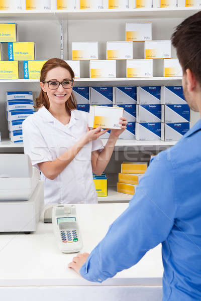 Happy Pharmacist Showing Drug To Client Stock photo © AndreyPopov