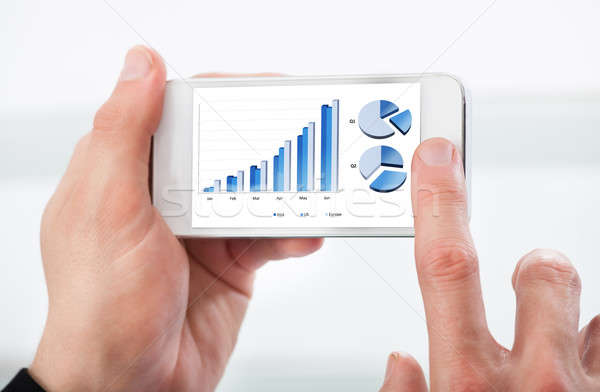 Man looking at a graph on his mobile phone Stock photo © AndreyPopov