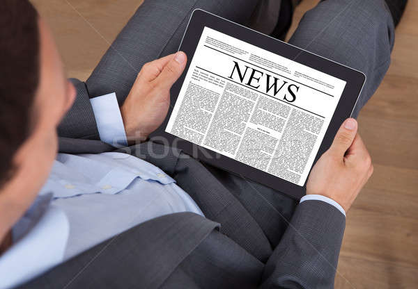 Stock photo: Businessman Reading News On Digital Tablet In Office