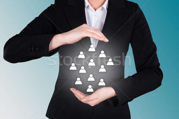 Businesswoman Protecting Human Icons Representing Leadership Stock photo © AndreyPopov