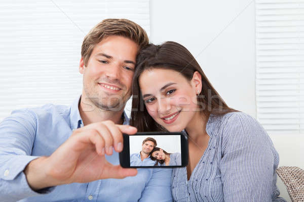 Couple Taking Self Portrait Through Smartphone At Home Stock photo © AndreyPopov