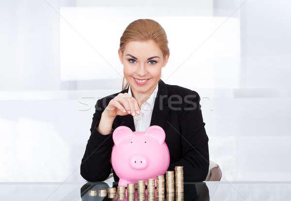Businesswoman Inserting Coin In Piggybank Stock photo © AndreyPopov