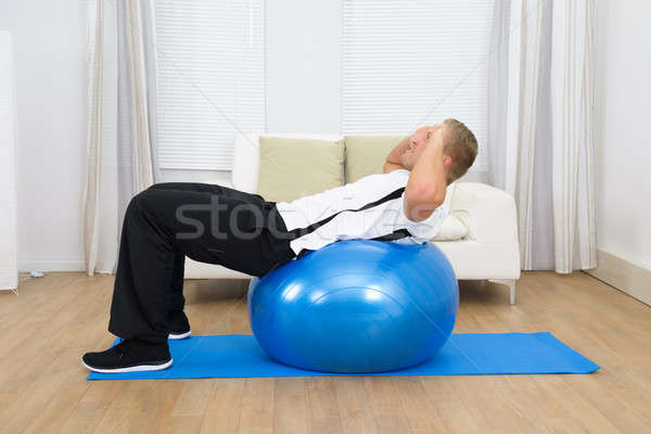 Man Leaning On Pilates Ball Doing Exercise Stock photo © AndreyPopov