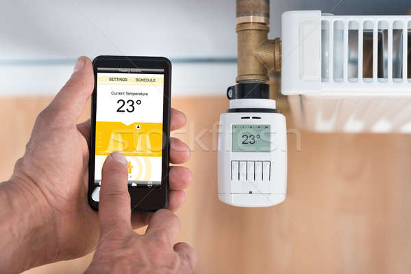 Person Hand Adjusting Temperature Of Thermostat Using Cellphone Stock photo © AndreyPopov