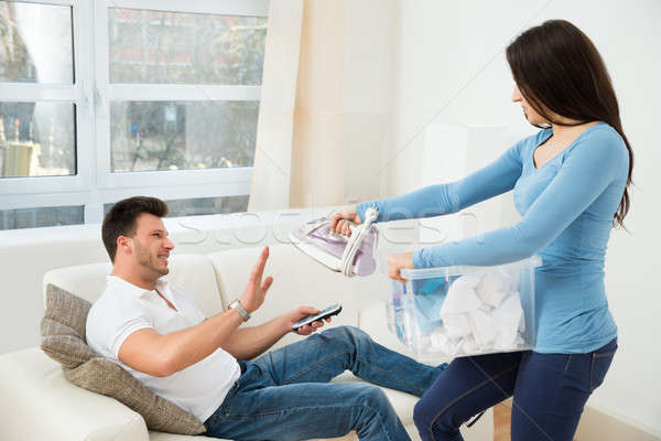 Woman Giving Iron To Man For Ironing Clothes Stock photo © AndreyPopov