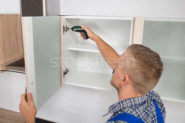 Carpenter Drilling In Cabinet Stock photo © AndreyPopov