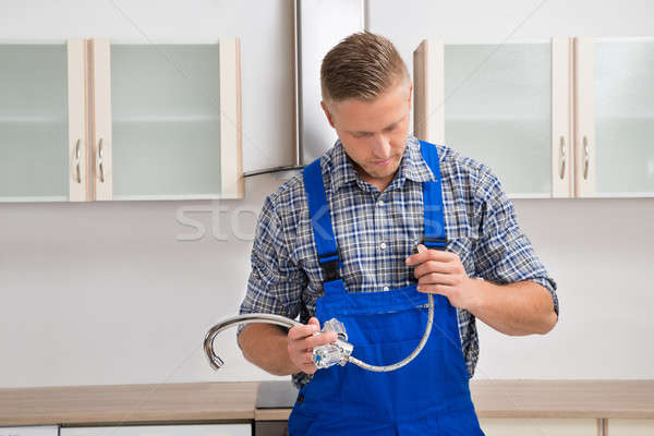 Plumber With Faucet In The Kitchen Room Stock photo © AndreyPopov