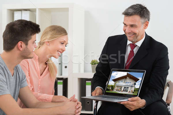 Estate Agent Showing House On Laptop To Couple Stock photo © AndreyPopov