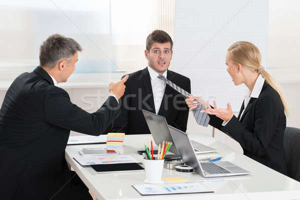 Two Businesspeople Quarreling To Young Businessman Stock photo © AndreyPopov