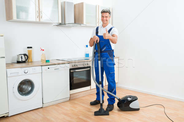 Portrait Of Janitor Cleaning Floor With Vacuum Cleaner Stock photo © AndreyPopov