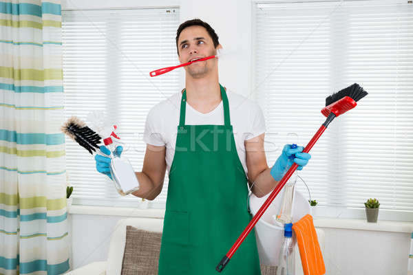Overburdened Cleaner Holding Cleaning Equipment Stock photo © AndreyPopov