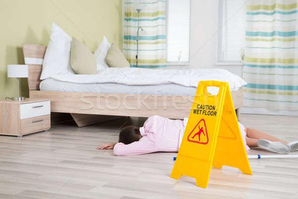 Vrouwelijke huishoudster bewusteloos nat vloer teken Stockfoto © AndreyPopov