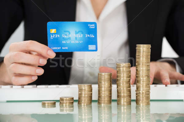 Businesswoman Holding Credit Card With Stacked Coins On Desk Stock photo © AndreyPopov