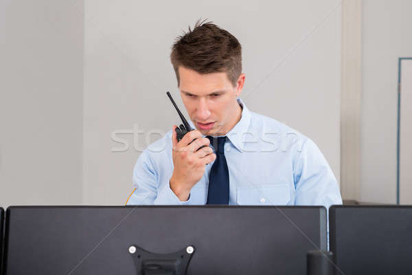 Security Guard Talking On Walkie-talkie In Control Room Stock photo © AndreyPopov