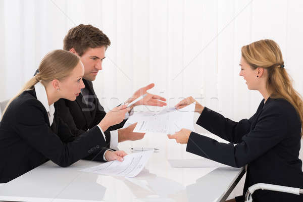 Colleague Showing Document To Businesspeople Stock photo © AndreyPopov