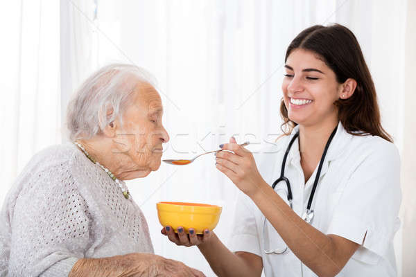 Female Doctor Feeding Soup To Senior Patient Stock photo © AndreyPopov