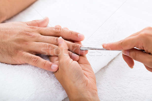 Manicurist Removing Cuticle From Person's Nail Stock photo © AndreyPopov