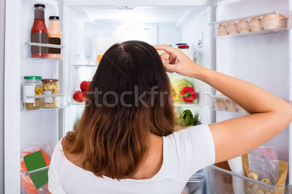 Confuso mulher comida geladeira Foto stock © AndreyPopov