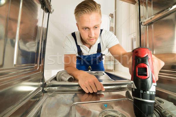 Człowiek zmywarka elektryczne wiercenia młody człowiek Zdjęcia stock © AndreyPopov