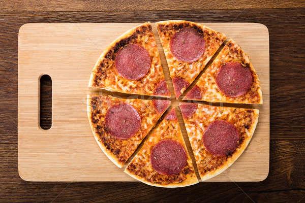 Tranches maison salami pizza délicieux planche à découper Photo stock © AndreyPopov
