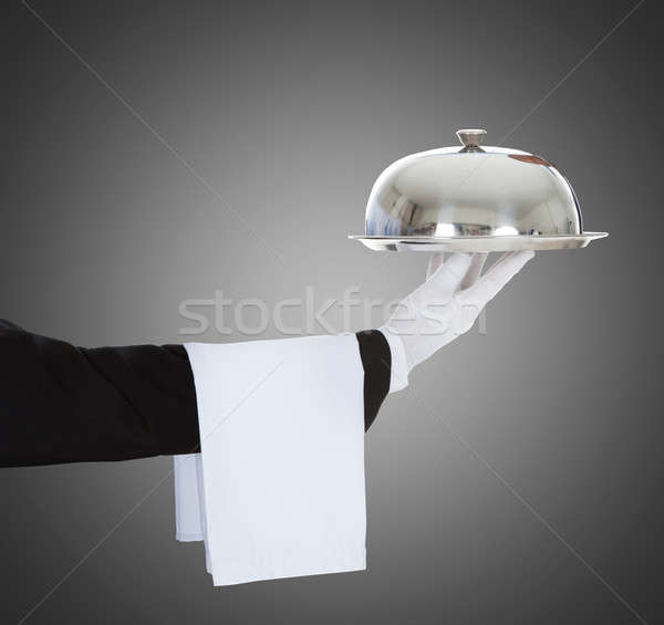 Stock photo: Waiter's Hand Holding Cloche And Tray