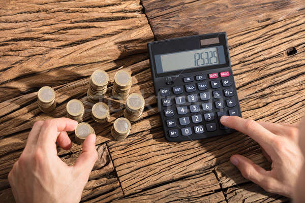 Person Calculating Coins On Calculator Stock photo © AndreyPopov