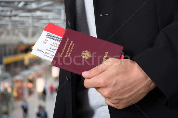 Male's Hand Holding Passport And Boarding Pass Stock photo © AndreyPopov