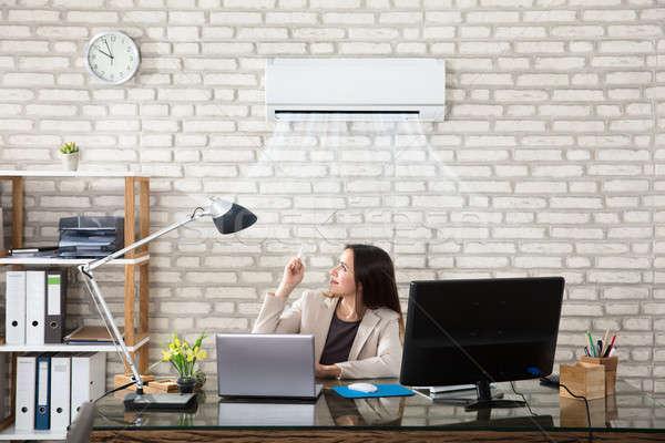 Businesswoman Operating Air Conditioner Stock photo © AndreyPopov