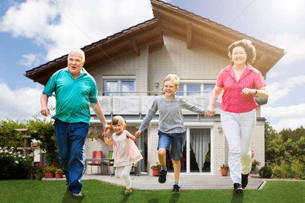 Nagyszülők fut unokák mosolyog ház kéz Stock fotó © AndreyPopov