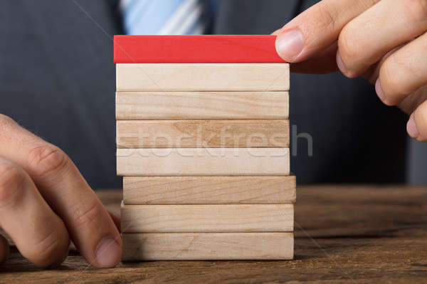 Businessman Placing Red Block On Wooden Tower At Table Stock photo © AndreyPopov
