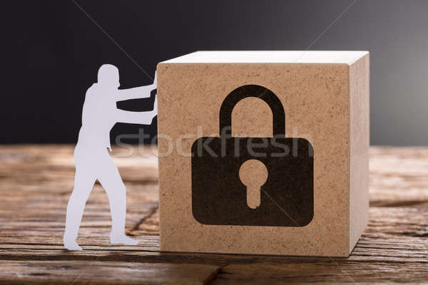 Paper Man Pushing Wooden Block With Padlock Sign Stock photo © AndreyPopov