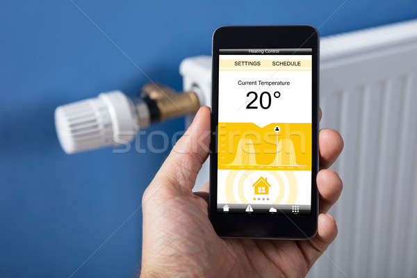 Person Hand Setting Temperature Of Thermostat Using Mobilephone Stock photo © AndreyPopov