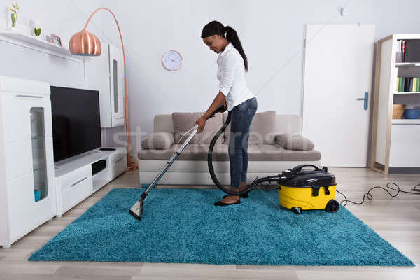 Woman Cleaning Carpet With Vacuum Cleaner Stock photo © AndreyPopov