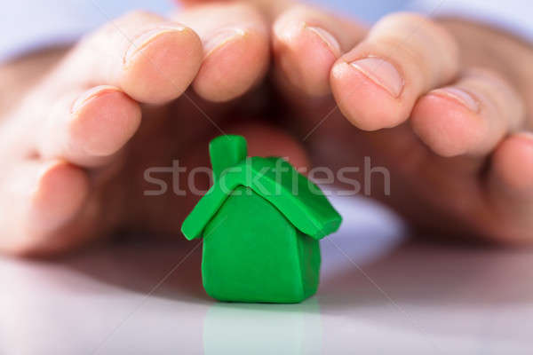Hands Protecting The Green Clay House Stock photo © AndreyPopov