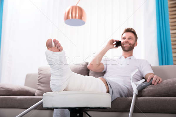 Stock photo: Happy Young Man With Broken Leg Talking On Smartphone