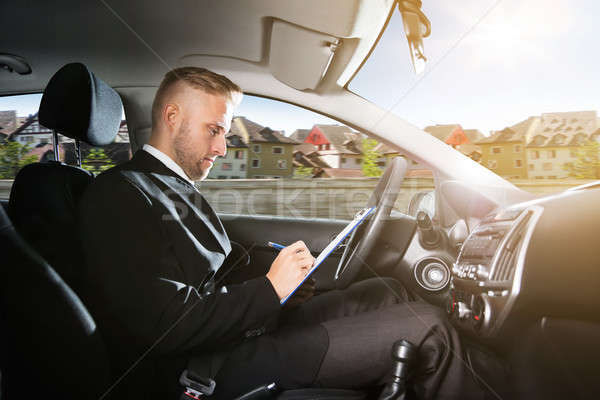 Man Writing On Clipboard Inside Self Driving Car Stock photo © AndreyPopov