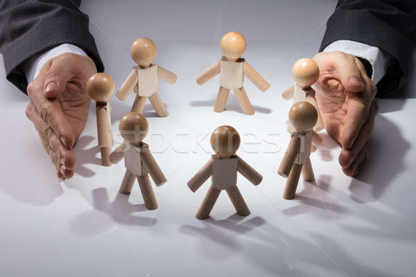 Human Hand Protecting Wooden Figures Stock photo © AndreyPopov