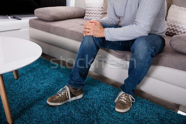 Homem sofrimento joelho dor sessão sofá Foto stock © AndreyPopov