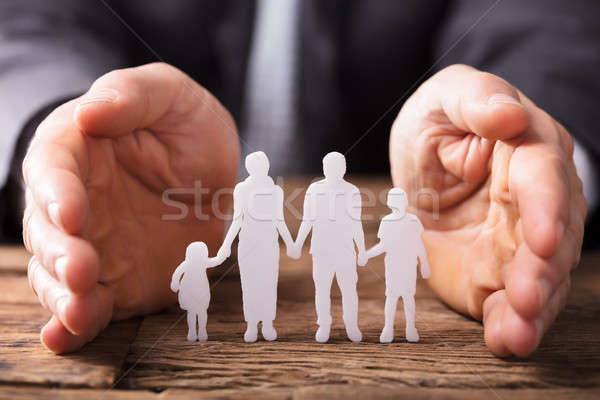 Businessperson's Hand Protecting Family Figures Stock photo © AndreyPopov