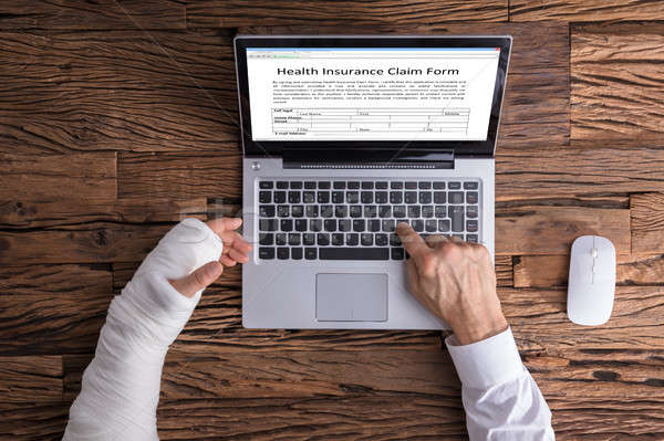 Stock photo: Person With Hand Injury Filling Health Insurance Claim Form