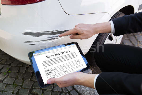 Person Examining Damaged Car While Filling Insurance Claim Form Stock photo © AndreyPopov